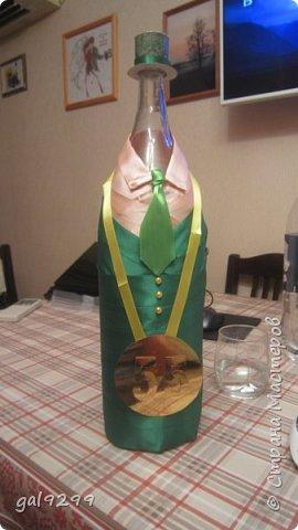Такую большую бутылку украсила дяде на День Рождения. За основу взята бутылка 1/4 ведра  - примерно 3 литра. Рубашка - персиковые ленты, костюм - зеленые ленты, галстук - салатовые ленты. Шляпа из зеленой с узором скрапбумаги. Медаль - из золотого картона, отдельно прикреплены цифры 55. Пуговички - полубусины. Все клеилось на клеевой пистолет. фото 1