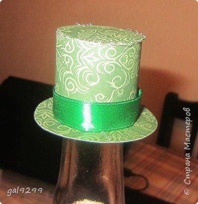 Такую большую бутылку украсила дяде на День Рождения. За основу взята бутылка 1/4 ведра  - примерно 3 литра. Рубашка - персиковые ленты, костюм - зеленые ленты, галстук - салатовые ленты. Шляпа из зеленой с узором скрапбумаги. Медаль - из золотого картона, отдельно прикреплены цифры 55. Пуговички - полубусины. Все клеилось на клеевой пистолет. фото 4