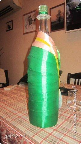 Такую большую бутылку украсила дяде на День Рождения. За основу взята бутылка 1/4 ведра  - примерно 3 литра. Рубашка - персиковые ленты, костюм - зеленые ленты, галстук - салатовые ленты. Шляпа из зеленой с узором скрапбумаги. Медаль - из золотого картона, отдельно прикреплены цифры 55. Пуговички - полубусины. Все клеилось на клеевой пистолет. фото 3