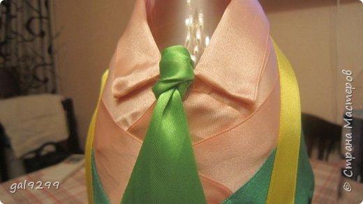 Такую большую бутылку украсила дяде на День Рождения. За основу взята бутылка 1/4 ведра  - примерно 3 литра. Рубашка - персиковые ленты, костюм - зеленые ленты, галстук - салатовые ленты. Шляпа из зеленой с узором скрапбумаги. Медаль - из золотого картона, отдельно прикреплены цифры 55. Пуговички - полубусины. Все клеилось на клеевой пистолет. фото 6