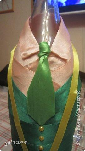 Такую большую бутылку украсила дяде на День Рождения. За основу взята бутылка 1/4 ведра  - примерно 3 литра. Рубашка - персиковые ленты, костюм - зеленые ленты, галстук - салатовые ленты. Шляпа из зеленой с узором скрапбумаги. Медаль - из золотого картона, отдельно прикреплены цифры 55. Пуговички - полубусины. Все клеилось на клеевой пистолет. фото 5