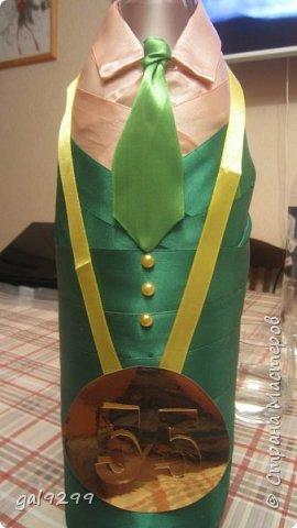 Такую большую бутылку украсила дяде на День Рождения. За основу взята бутылка 1/4 ведра  - примерно 3 литра. Рубашка - персиковые ленты, костюм - зеленые ленты, галстук - салатовые ленты. Шляпа из зеленой с узором скрапбумаги. Медаль - из золотого картона, отдельно прикреплены цифры 55. Пуговички - полубусины. Все клеилось на клеевой пистолет. фото 7