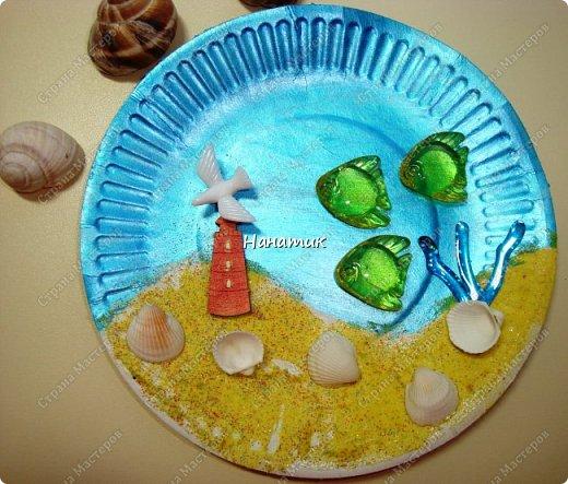 Добрый день. Это панно из одноразовой тарелки Алина сделала на День Рождения. Одноразовую тарелку дочурка покрасила краской акриловой - это море. У нас остался песок разноцветный с одного набора.Алина мазала пва и насыпала песок. Приклеила маяк. Так как чайку-фигурку не нашли, то приклеили голубя))) Дальше дочурка приклеила фигурки рыбок на горячий клей, и ракушки.  фото 1