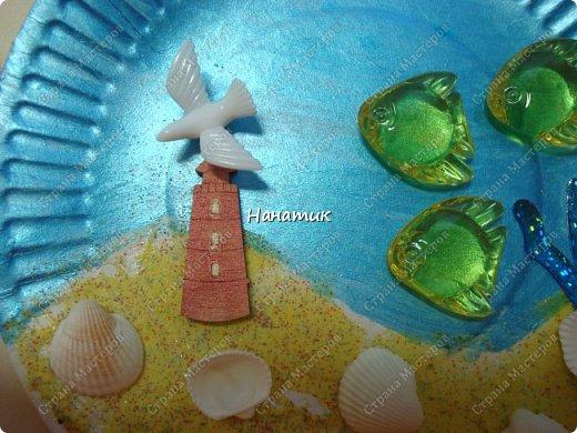 Добрый день. Это панно из одноразовой тарелки Алина сделала на День Рождения. Одноразовую тарелку дочурка покрасила краской акриловой - это море. У нас остался песок разноцветный с одного набора.Алина мазала пва и насыпала песок. Приклеила маяк. Так как чайку-фигурку не нашли, то приклеили голубя))) Дальше дочурка приклеила фигурки рыбок на горячий клей, и ракушки.  фото 2