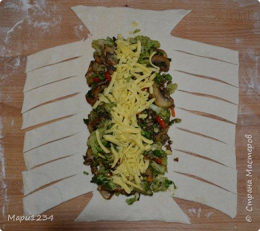 Лист слоеного теста раскатываем, кладем на середину любую начинку и нарезаем такие полоски, чтобы потом их переплести. фото 1
