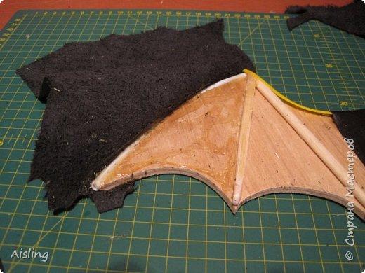 """""""Крадущийся в ночи""""  Редкий ночной нетопырь, Размах крыльев около 40 сантиметров. Вес - около килограмма. Миловидный, но коварный и опасный!   Материалы: 1) фанера толщиной 4 мм  (для основы) 2) куски чёрной кожи - для внешней стороны зверушки 3) любая ткань - для внутренней отделки, и небольших внешних элементов 4) глаза - красный фетр 5) перепонки в крыльях - палочки от китайской лапши и трубочки от воздушных шариков 6) нос - перламутровая пуговка с двумя дырками 7) лапки - две ложки из БаскинРобинса, (потом заменены на лапки, вырезанные из старого ремня) 8) пузико - кусок серого поролона, обтянутый тканью 9) пузико крепится двумя болтами от ремня. 10) для соединения всего, нужны ещё несколько болтов и гаек. 11) для украшения крыльев - звёздочки с гвоздиками, оставшиеся от какой-то аппликации 12) бантик. 13) крепление с кольцом, чтобы вешать на стену + два шурупа к нему  инструменты: 1) лобзик  2) клеевой пистолет 3) нож, ножницы и скальпель (для кожи и ткани) 4) молоток и пинцет 5) клей, типа """"момент"""" и типа """"суперклей"""" 6) шуруповёрт  +  перчатки и пылесос! фото 6"""