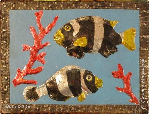 Рыбы и кораллы. Размер 25х19 см Основа панно - ДСП (древесно-стружечная плита), окрашенная голубой краской. Рыбы и кораллы вырезаны из жести, обработаны чеканкой и окрашены акриловой краской. Для лучшего эффекта использован разноцветный глиттер (блёстки). На снимке блёстки не просматриваются. фото 1