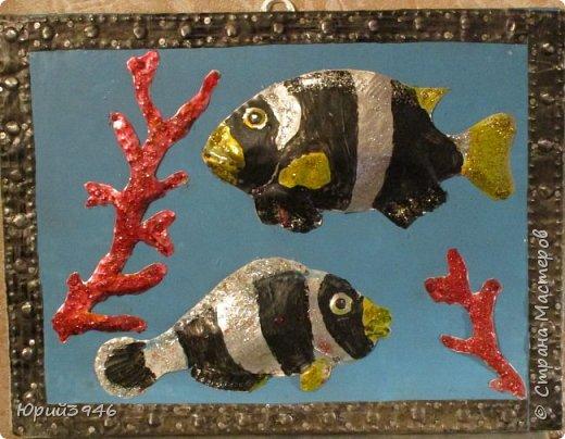 Рыбы и кораллы. Размер 25х19 см Основа панно - ДСП (древесно-стружечная плита), окрашенная голубой краской. Рыбы и кораллы вырезаны из жести, обработаны чеканкой и окрашены акриловой краской. Для лучшего эффекта использован разноцветный глиттер (блёстки). На снимке блёстки не просматриваются. фото 2