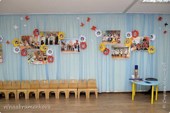Много лет занимаюсь оформлением актового зала к праздникам. Накопилась целая коллекция. Представляю  композицию из объёмных бумажных цветов. Это центральная стена. фото 2