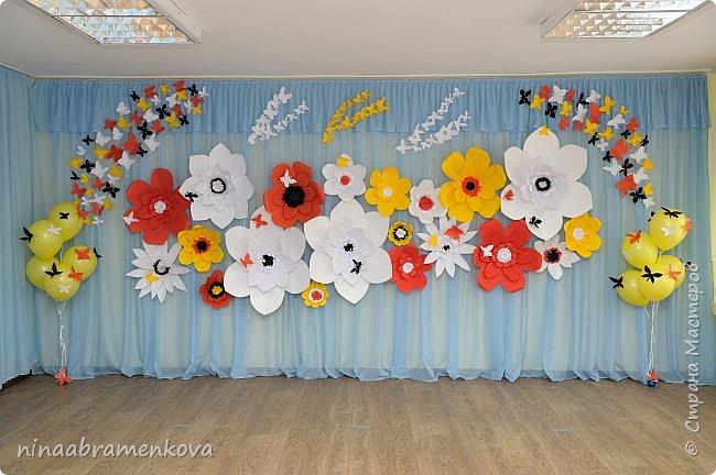 Много лет занимаюсь оформлением актового зала к праздникам. Накопилась целая коллекция. Представляю  композицию из объёмных бумажных цветов. Это центральная стена. фото 1
