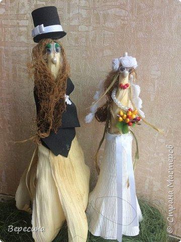 """Здравствуйте , дорогие жители Страны мастеров. Скоро грядёт праздник осени, и я вспомнила про свою прошлогоднюю поделку, сотворённую за вечер. Так как торопилась, то МК снять как-то не было времени.  За основу взяла 2 кукурузных початка -  один побольше - это жених, а маленький - это невеста. У жениха """"волосики"""" - борода, а у невесты """"волосики"""" кукурузные сзади - это волосы. Цилиндр на голову  жениха склеила из чёрного фоамирана, приделав сбоку маленький бантик из 6-мм репсовой ленты, а у невесты на голове веночек из кружева в виде розочек( я просто отрезала полоску шириной в одну розочку. Глаза - это """"бегающие"""" глазки для поделок, носы - английские булавки с белыми бусинками на конце, у невесты губки из булавок с красными бусинами. Жениху сделала фрак из чёрного фоамирана - отрезала прямоугольник, обернула туловище, на груди отогнула лацканы и закрепила незаметно булавкой, на лацкан прицепила плоский белый цветочек, отрезанный от тесьмы. Невесте сделала юбочку из белой гофрированной бумаги, повязав сверху на талии поясок из репсовой 6-мм ленты, за этот поясок вставила букетик из тычинок, а на шею - нитка бус из бисера.  Муж эту парочку прикрутил шурупами к деревянной рейке, которую я декорировала зелёным сизалем. Всё. За зиму поделка слегка """"схуднула"""" , но держится крепко. У жениха , правда, брюки - кукурузные листья, частично  развернулись, а у невесты только талия стала тоньше. Буду рада если кто-то воспользуется моей идеей и на скорую руку смастерит вот такую сладкую парочку! фото 1"""