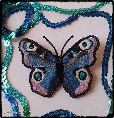 Бабочка вышита на фетре нитками мулине (использованы 14 цветов), тельце декорировано стеклярусом, крылья прошиты металлизированной золотой нитью.