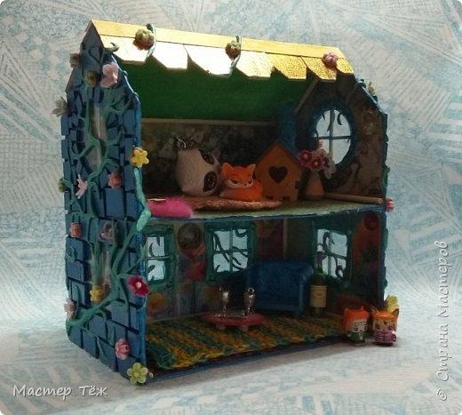 Давным-давно у меня поселились две милые игрушки, которые запали в самую глубину художника!  И как-то сам-собой взялся картон от коробки, скотч, линейка, карандаш. Час я усердно работал над чертежом, измерял размеры, формы и причуды кукольного строительства. Так появилось это жилище — домик двух маленьких жильцов.   Оформление затянулось на полгода или чуть больше этого, т.к. собирал я его для себя, для любования и радости. Мне хотелось строго взвесить каждую деталь будущего интерьера, поэтому сборка заняла много времени.   Но сегодня я сделал последний штрих — приклеил маленькие цветы на фасад. И… проект был наконец-то завершен.  фото 5