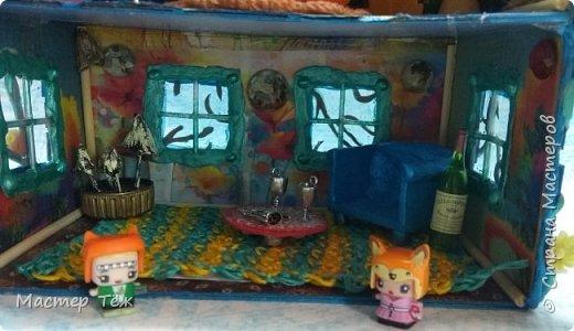 Давным-давно у меня поселились две милые игрушки, которые запали в самую глубину художника!  И как-то сам-собой взялся картон от коробки, скотч, линейка, карандаш. Час я усердно работал над чертежом, измерял размеры, формы и причуды кукольного строительства. Так появилось это жилище — домик двух маленьких жильцов.   Оформление затянулось на полгода или чуть больше этого, т.к. собирал я его для себя, для любования и радости. Мне хотелось строго взвесить каждую деталь будущего интерьера, поэтому сборка заняла много времени.   Но сегодня я сделал последний штрих — приклеил маленькие цветы на фасад. И… проект был наконец-то завершен.  фото 8