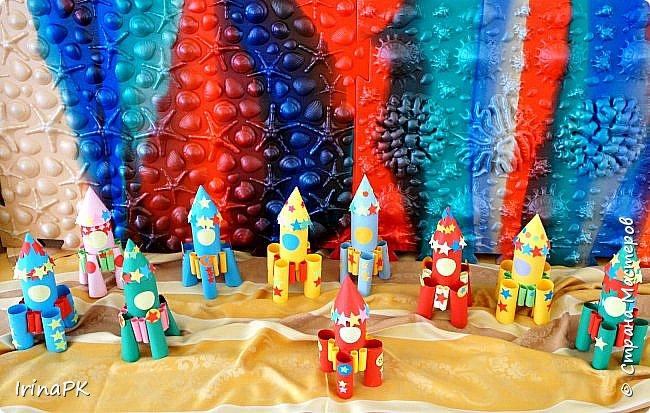 Такие ракеты делала с детьми ко Дню Космонавтики уже давно, забыла выложить. Основа ракеты - трубочка от туалетной бумаги, обклеенная цветной бумагой. Верх - конус. Сопла - накручиваем бумагу на толстый маркер, между ними - трубочки, накрученные на фломастеры. Можно скрутить ровно, а можно в виде кулечков. фото 8