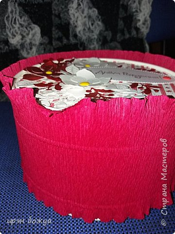 Я продолжаю декорировать имеющиеся коробочки. Это коробка от рафаэлло. Круглая. Цветовая гамма соответствующая бело-красная. Бока коробочки задекорированы гофрированной бумагой. А сверху украсила вырубкой и дотсами. Внутри конфеты покупные ассорти. фото 2