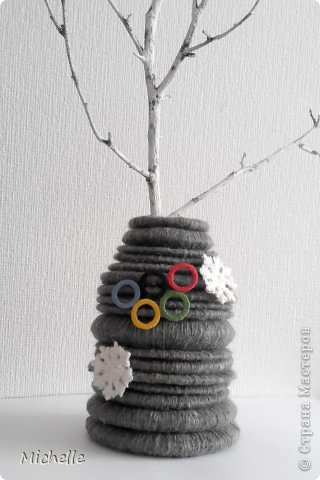 Ваза из шерстяных колец, сложенных пирамидкой. Неизменная Олимпийская эмблема - олимпийские кольца. Они символизируют единство пяти частей света и всемирный характер Олимпийских Игр. Кольца, а также снежинки - Олимпиада ведь зимняя, и стали украшением моей вазы. За основу самой вазы я тоже решила взять кольцо. фото 1