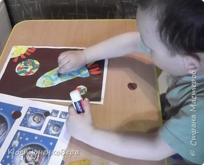 Работа моего внука Коли в технике обрывной аппликации. Ему 3,5 года. С композицией помогла я, вырезала из цветного листа ракету и планеты.  фото 5