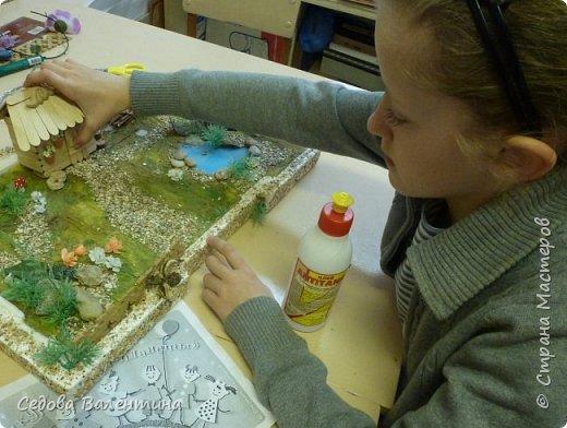 """Творческий проект """"Мой прекрасный сад"""", выполнен Демченко Алёной, ученицей 2 класса. Это макет, где используются бросовые материалы и декоративные растения, камни, песок, деревянные палочки...Нам хотелось создать маленький уютный садик, в центре макета стоит деревянный домик, есть небольшой пруд, альпийская горка, можно босиком ходит по траве и дорожке посыпанной мелким песком. Под елью стоит деревянная скамейка,на которой можно отдохнуть в жару.По саду ходят курочки и петушок утром рано сообщает о начале нового дня своим громким кукареканьем... фото 7"""