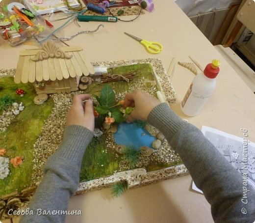 """Творческий проект """"Мой прекрасный сад"""", выполнен Демченко Алёной, ученицей 2 класса. Это макет, где используются бросовые материалы и декоративные растения, камни, песок, деревянные палочки...Нам хотелось создать маленький уютный садик, в центре макета стоит деревянный домик, есть небольшой пруд, альпийская горка, можно босиком ходит по траве и дорожке посыпанной мелким песком. Под елью стоит деревянная скамейка,на которой можно отдохнуть в жару.По саду ходят курочки и петушок утром рано сообщает о начале нового дня своим громким кукареканьем... фото 8"""
