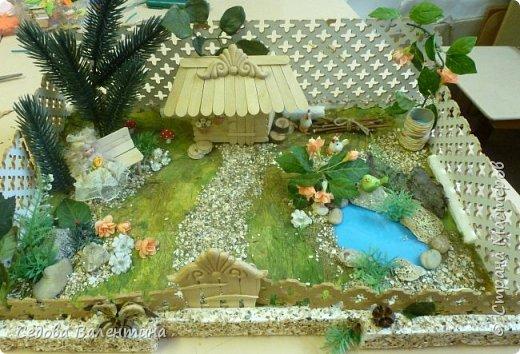 """Творческий проект """"Мой прекрасный сад"""", выполнен Демченко Алёной, ученицей 2 класса. Это макет, где используются бросовые материалы и декоративные растения, камни, песок, деревянные палочки...Нам хотелось создать маленький уютный садик, в центре макета стоит деревянный домик, есть небольшой пруд, альпийская горка, можно босиком ходит по траве и дорожке посыпанной мелким песком. Под елью стоит деревянная скамейка,на которой можно отдохнуть в жару.По саду ходят курочки и петушок утром рано сообщает о начале нового дня своим громким кукареканьем... фото 1"""