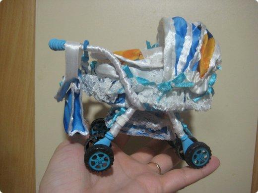 Здравствуйте, уважаемые мастера и мастерицы, представляю Вашему вниманию свою конкурсную работу - малыша в коляске, у которого есть любимые игрушки - мишутка и погремушка. Малыш слеплен из полимерной глины, а коляска сшита из ткани, на проволочном каркасе с подвижными колесиками. Этот мальчик с пальчик имеет росточек небольшой - около 53 мм. В своем юном, 4-месячном возрасте мальчик любит играть в погремушки, сосать соску, а также сжимать ручки в кулачки. А самая лучшая и самая любимая для него игрушка - это плюшевый медвежонок Тэдди, которого он берет с собой  в коляску на прогулку. фото 2