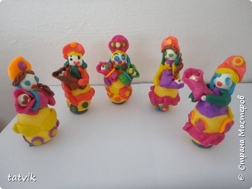 Среди современных русских глиняных игрушек самой большой известностью и популярностью пользуется дымковская (в прошлом вятская) игрушка. Это обобщенная, декоративная глиняная скульптура, близкая к народному примитиву: фигурки высотой в среднем 15-25 см, разукрашенные по белому фону многоцветным геометрическим орнаментом из кругов, горохов, полос, клеток, волнистых линий, яркими красками, часто с добавлением золота.  Именно из- за своей яркости дымковские фигурки очень нравятся детям.  Мы с девочками решили слепить вот таких куколок на основе футляра от киндер-сюрприза. Он очень похож на юбку-колокол дымковской барыни.  фото 14