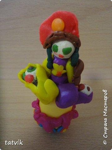 Среди современных русских глиняных игрушек самой большой известностью и популярностью пользуется дымковская (в прошлом вятская) игрушка. Это обобщенная, декоративная глиняная скульптура, близкая к народному примитиву: фигурки высотой в среднем 15-25 см, разукрашенные по белому фону многоцветным геометрическим орнаментом из кругов, горохов, полос, клеток, волнистых линий, яркими красками, часто с добавлением золота.  Именно из- за своей яркости дымковские фигурки очень нравятся детям.  Мы с девочками решили слепить вот таких куколок на основе футляра от киндер-сюрприза. Он очень похож на юбку-колокол дымковской барыни.  фото 12