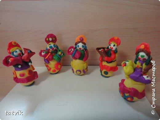Среди современных русских глиняных игрушек самой большой известностью и популярностью пользуется дымковская (в прошлом вятская) игрушка. Это обобщенная, декоративная глиняная скульптура, близкая к народному примитиву: фигурки высотой в среднем 15-25 см, разукрашенные по белому фону многоцветным геометрическим орнаментом из кругов, горохов, полос, клеток, волнистых линий, яркими красками, часто с добавлением золота.  Именно из- за своей яркости дымковские фигурки очень нравятся детям.  Мы с девочками решили слепить вот таких куколок на основе футляра от киндер-сюрприза. Он очень похож на юбку-колокол дымковской барыни.  фото 15